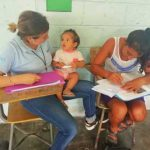Mujer estudiando mientras su maestra cuida a su hija